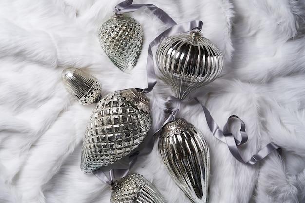 Boże narodzenie lub nowy rok dekoracji tło. snowy zabawki choinkowe na tle białego futra, zbliżenie