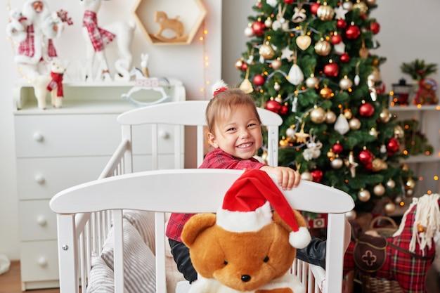Boże narodzenie mała uśmiechnięta dziewczyna w białym łóżku w children pokoju