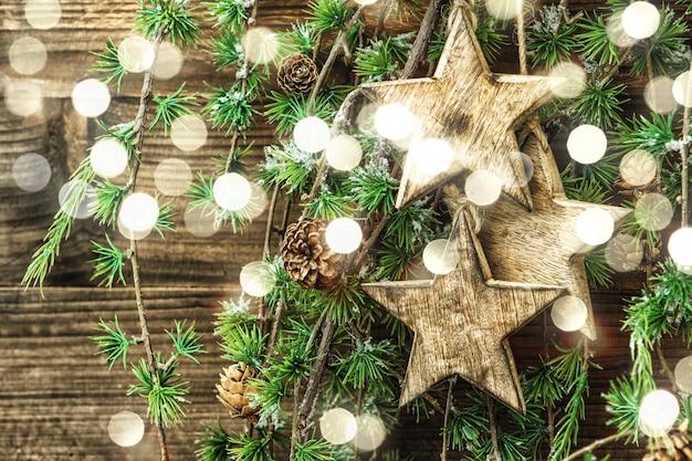 Boże narodzenie martwa natura drewniane ozdoby i gałęzie sosny. dekoracje w stylu vintage. retro stonowana z efektem świetlnym