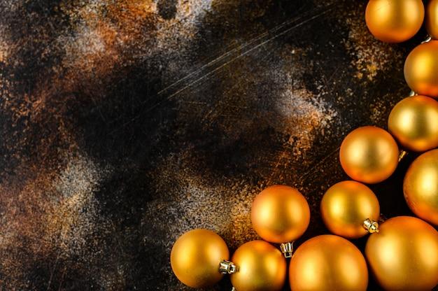 Boże narodzenie mieszkanie świeckich, tło nowego roku. złote bombki na ciemnym tle.