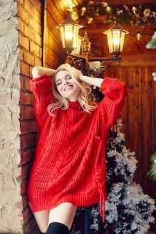 Boże narodzenie moda seksowna kobieta blondynka w czerwonym swetrze, zabawy i pozowanie na choince i latarni. zima i choinka w wiejskim domu. dziewczyna z idealną figurą i uśmiechem