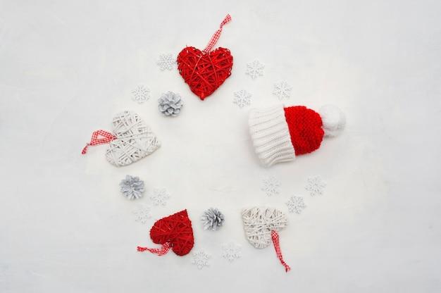 Boże narodzenie najlepsze ujęcie ramki ze stożków, serc i płatków śniegu, ozdobione czapką mikołaja