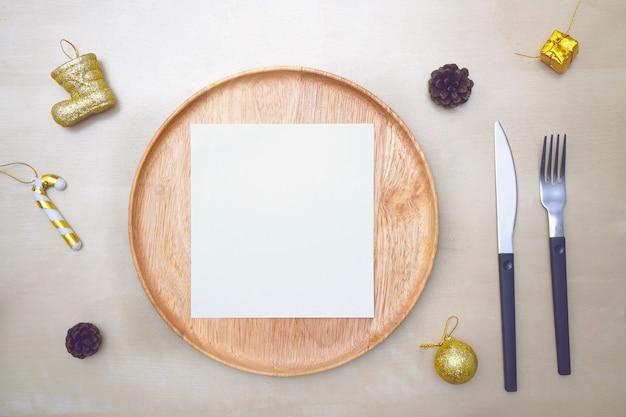 Boże narodzenie nakrycie stołu. drewniany talerz i sztućce na drewnie. widok z góry.