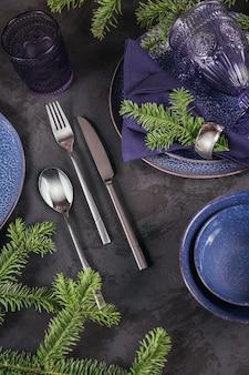 Boże narodzenie nakrycie stołu. granatowa dekoracja z gałązką jodły. talerze, kieliszki do wina i sztućce z dekoracyjną tkaniną na ciemnym tle. widok płaski, widok z góry.