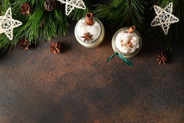 Boże narodzenie napój ajerkoniak w słoiku mason z cynamonem i gałką muszkatołową na brązowym tle. widok z góry. skopiuj miejsce.