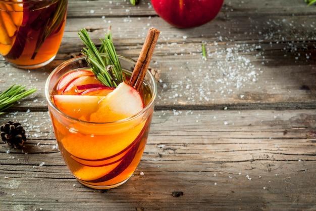 Boże narodzenie, napoje na święto dziękczynienia. jesień, zimowy grog koktajlowy, gorąca sangria, grzane wino - jabłko, rozmaryn, cynamon, anyż. na starym rustykalnym drewnianym stole. ze stożkami, gałązkami rozmarynu. skopiuj miejsce