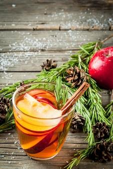 Boże narodzenie, napoje na święto dziękczynienia. jesień, zimowy grog koktajlowy, gorąca sangria, grzane wino jabłkowe, rozmaryn, cynamon, anyż. na starym rustykalnym drewnianym stole. ze szyszkami, rozmarynem.