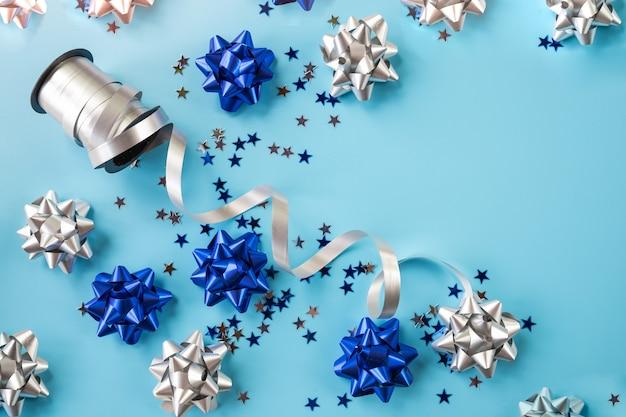Boże narodzenie niebieskie i srebrne wakacje wstążka łuk na niebieskim tle. magiczna karta z pozdrowieniami świątecznymi. błyszczące niebieskie wstążki. świąteczna kokardka