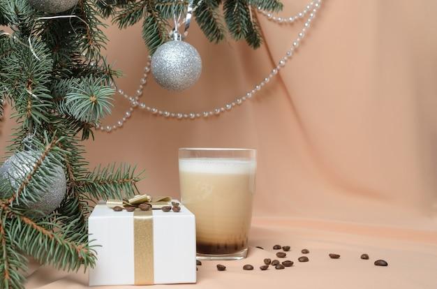 Boże narodzenie. noworoczna kompozycja wykonana z gałęzi choinki, pudełka na prezenty, szklanego kubka z kawą i mlekiem. selektywne skupienie.