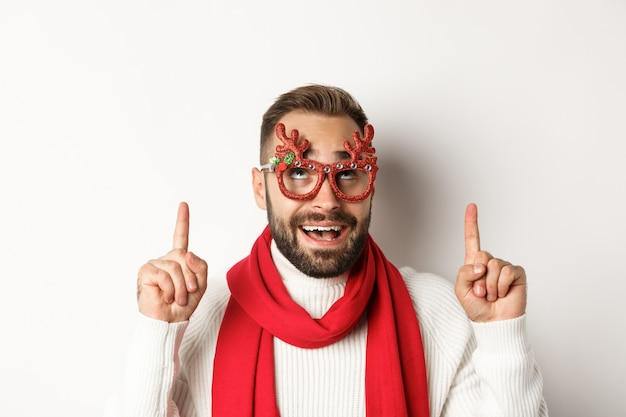 Boże narodzenie, nowy rok i koncepcja uroczystości. zbliżenie: podekscytowany brodaty facet w imprezowych okularach, wskazując i patrząc na promocję sklepu, białe tło