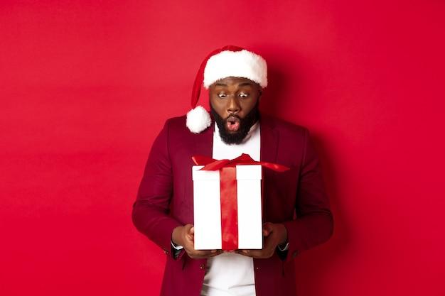 """Boże narodzenie, nowy rok i koncepcja zakupów. zaskoczony murzyn wpatrujący się w świąteczny prezent, mówiący """"wow, zdumiony"""", otrzymujący prezent świąteczny, czerwone tło"""