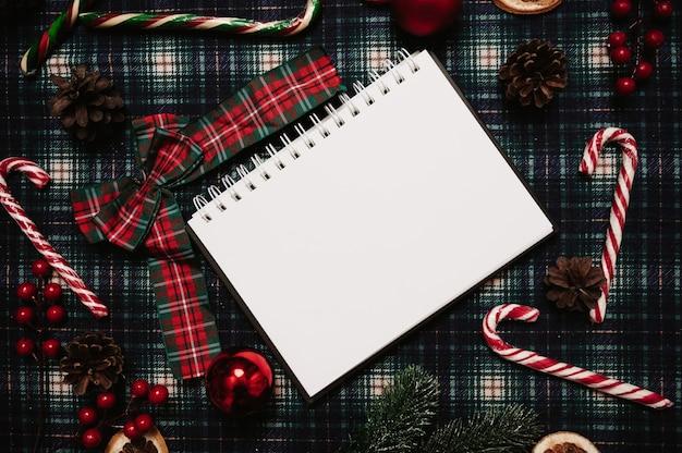 Boże narodzenie nowy rok papierowa ramka, styl flatley z widokiem z góry z ozdobami świątecznymi wykonanymi z kulek, stożków, laski świąteczne na tle w klatce. miejsce na twój tekst