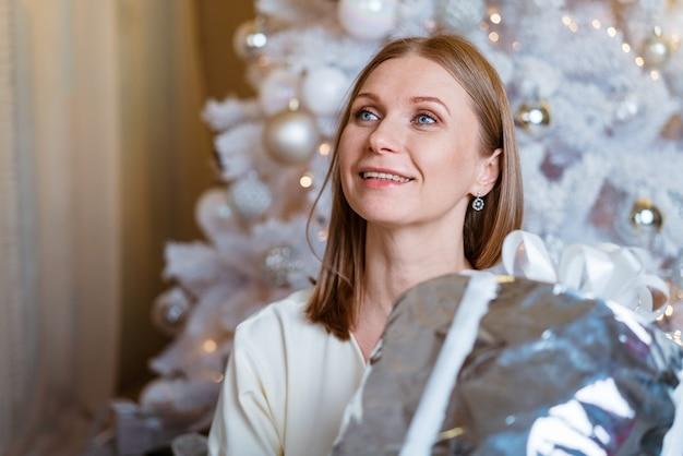Boże narodzenie nowy rok piękna kobieta w lekkiej sukience i skarpetkach siedzi na podłodze z świątecznym pudełkiem ...