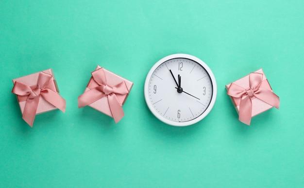 Boże narodzenie, nowy rok. pudełka na prezenty z zegarem na tle zielonej mięty. widok z góry