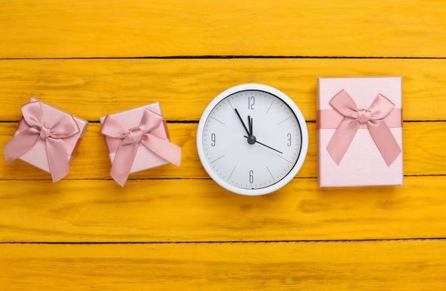 Boże narodzenie, nowy rok. pudełka na prezenty z zegarem na żółtej drewnianej powierzchni. widok z góry