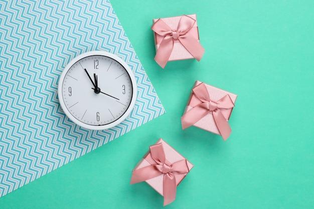 Boże narodzenie, nowy rok. pudełka prezentowe z zegarem na miętowo-zielonej i niebieskiej powierzchni. widok z góry