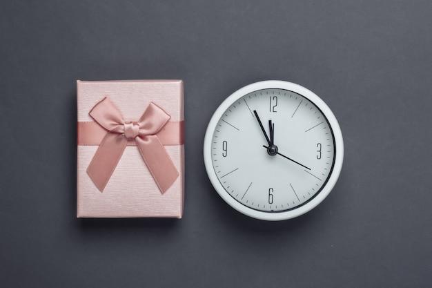 Boże narodzenie, nowy rok. pudełko prezentowe z zegarem na szarej powierzchni. widok z góry