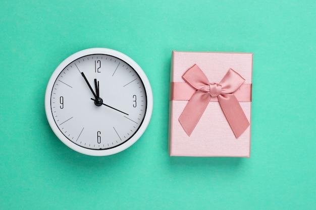 Boże narodzenie, nowy rok. pudełko z zegarem na tle zielonej mięty. widok z góry