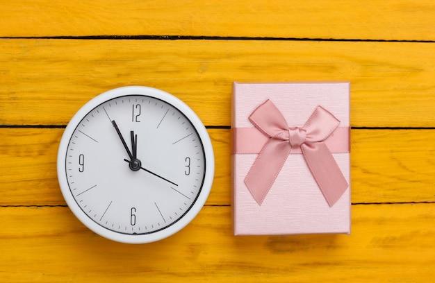 Boże narodzenie, nowy rok. pudełko z zegarem na żółtej drewnianej powierzchni. widok z góry