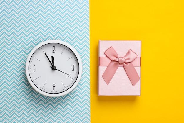 Boże narodzenie, nowy rok. pudełko z zegarem na żółto-niebieskiej powierzchni. widok z góry