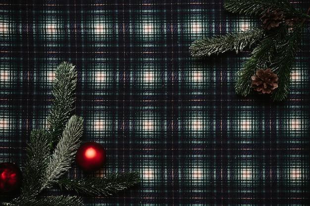 Boże narodzenie nowy rok rama, styl flatley z widokiem z góry z ozdób choinkowych z szyszek, gałęzi jodły na tle w klatce, miejsce na twój tekst