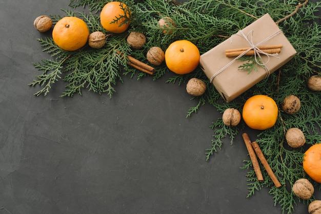 Boże narodzenie nowy rok skład z pudełka mandarynki szyszki sosnowe zieloni w czarnym tle dekoracja świąteczna stonowanych