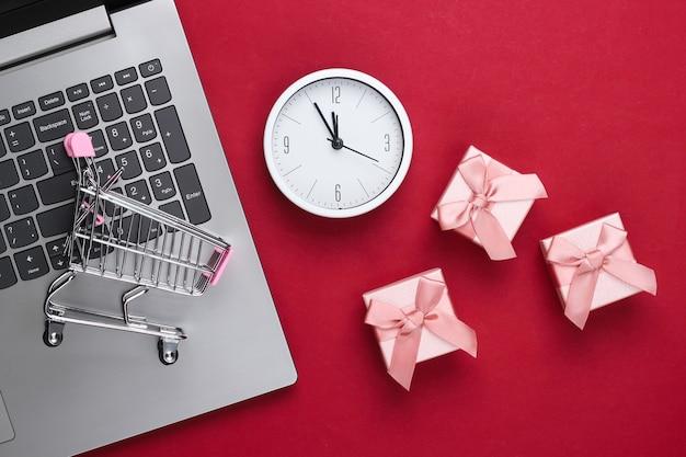 Boże narodzenie, nowy rok zakupy online. laptop, wózek mini supermarketu z pudełkami na prezenty, zegar na czerwonym tle. widok z góry
