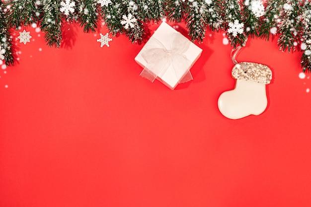 Boże narodzenie obraz z białym pudełkiem i piernikiem na gałęzie jodły z płatkami śniegu i śniegiem na czerwono.