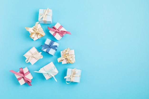 Boże narodzenie ornamety i pudełka na prezenty ułożone w kształcie choinki na niebieskiej powierzchni