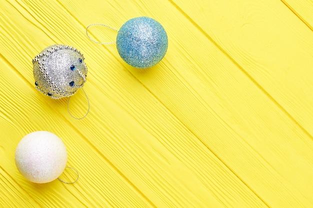 Boże narodzenie ozdobne kulki na żółtym tle.