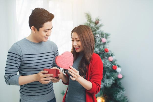 Boże narodzenie para azji. przystojny mężczyzna daje swojej dziewczynie/żonie prezent w domu świętując nowy rok ludzie