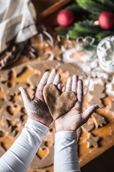 Boże narodzenie pieczenia i pierniki serca w ręce kobiety.