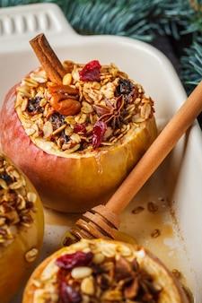 Boże narodzenie pieczone jabłka z muesli, żurawiną, orzechami i miodem w naczyniu piekarnika, ciemne tło.