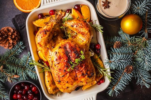 Boże narodzenie pieczony kurczak z żurawiną, pomarańczą, przyprawami i ziołami. boże narodzenie jedzenie koncepcja.