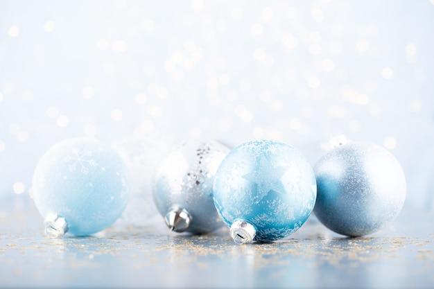 Boże narodzenie piłka tło. ozdoby z życzeniami na niebieskim tle bokeh.
