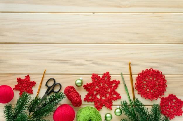 Boże narodzenie płaskie układanie elementów do robótek ręcznych. dziane płatki śniegu, nici i haczyki na drewnie