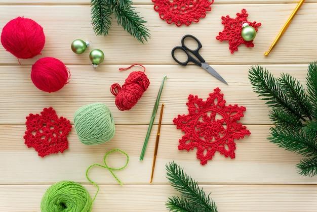 Boże narodzenie płaskie układanie elementów do robótek ręcznych. dziane płatki śniegu, nici i haczyki na podłoże drewniane.