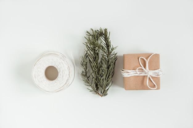 Boże narodzenie. płaskie ukształtowanie pudełka na prezent rzemiosła bożego narodzenia na białym tle. ręcznie robione brązowe pudełko papierowe z gałązką choinki i białym sznurkiem.
