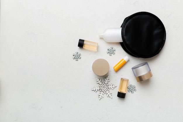 Boże narodzenie płasko leżał z kosmetykami do makijażu w kosmetyczce na kolorowym tle. widok z góry koncepcja piękna nowego roku.
