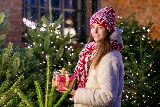 Boże narodzenie portret pięknej dziewczyny w ciepłe ubrania i szalik stojący na ulicy udekorowanej na nowy rok na tle choinki z prezentem w dłoniach.