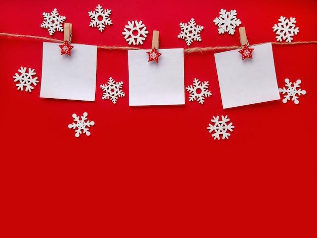 Boże narodzenie powierzchnia z płatkami śniegu. trzy kartki tekstu z pozdrowieniami wiszą na sznurku na jaskrawoczerwonej ścianie. widok z góry, miejsce na tekst, miejsce na tekst.