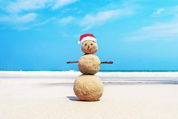 Boże narodzenie pozytywne sandy snowman w czerwonym kapeluszu świętego mikołaja na plaży zachód słońca nad oceanem. noworoczne zniżki na wakacje w koncepcji miejsc w gorących krajach