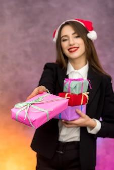 Boże narodzenie przedstawia koncepcję. piękna kobieta trzymająca kolorowe pudełka na prezenty