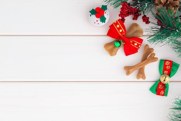 Boże narodzenie psy tło. kość ścięgna owinięta czerwono-zieloną wstążką świąteczną na białym drewnie