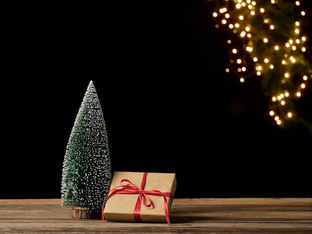 Boże narodzenie pudełko i jodła na drewnianym stole przed niewyraźne świąteczne światła, miejsce na tekst