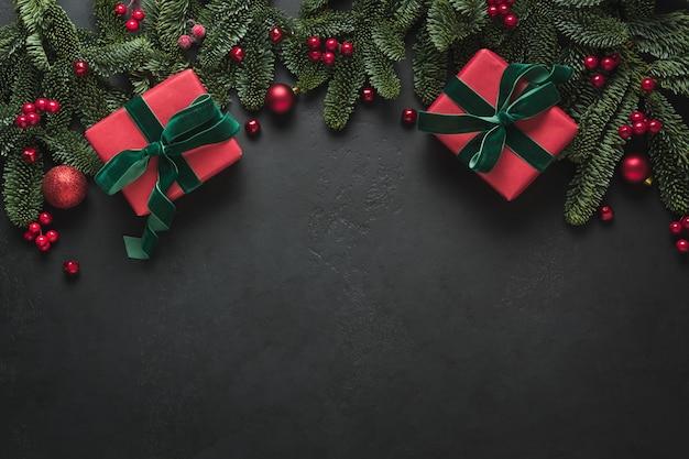 Boże narodzenie rama z czerwonymi prezentami i gałęziami jodły