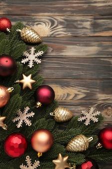 Boże narodzenie ramki - gałęzie drzew z czerwonymi i złotymi bombkami, gwiazdy, płatki śniegu na brązowym tle. zdjęcie pionowe