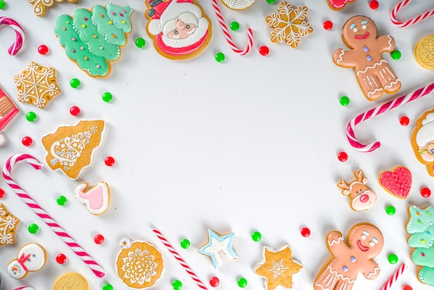 Boże narodzenie ramki słodycze. różne świąteczne słodycze świąteczne, tradycyjne słodycze i ciasteczka. flatlay z cukierkami z trzciny cukrowej, piernikiem, słodyczami, widok z góry