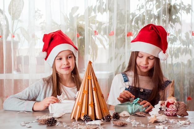 Boże narodzenie ręcznie. dziewczyny przygotowują ekologiczne prezenty furoshiki. zero marnowania