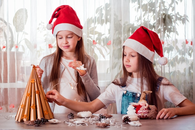 Boże narodzenie ręcznie. dziewczyny przyklejają gwiazdki na drzewku z papieru czerpanego i przygotowują girlandę